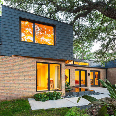 Example of a large trendy red two-story mixed siding exterior home design in Houston