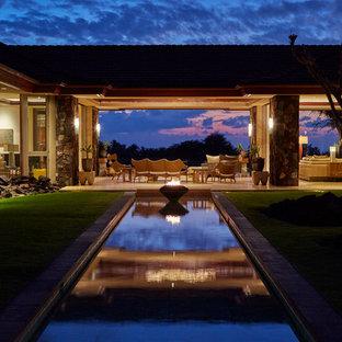 Idee per la facciata di una casa grande beige tropicale a un piano con rivestimento in stucco e tetto a padiglione