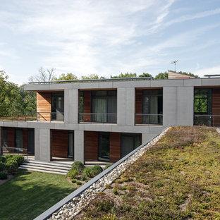 Modelo de fachada de casa gris, minimalista, grande, de dos plantas, con revestimiento de hormigón, tejado plano y techo verde