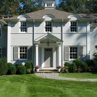 Diseño de fachada blanca, clásica, de dos plantas, con revestimiento de ladrillo
