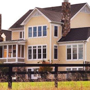 Example of a large classic yellow three-story wood exterior home design in DC Metro with a shingle roof