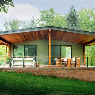 他の地域のミッドセンチュリースタイルのおしゃれな家の外観 (ビニールサイディング、緑の外壁) の写真