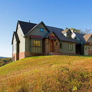 Imagen de fachada de casa verde, clásica, de tamaño medio, de una planta, con revestimiento de aglomerado de cemento, tejado a dos aguas y tejado de teja de madera