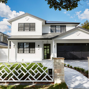 Large transitional two-storey white house exterior in Sydney with wood siding, a gable roof and a metal roof.