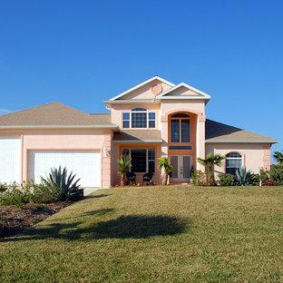 Exemple d'une façade de maison rose exotique de taille moyenne et de plain-pied avec un revêtement en stuc, un toit à quatre pans et un toit en shingle.