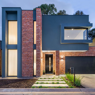 Photo of a contemporary two-storey brick red house exterior in Adelaide with a flat roof and a metal roof.