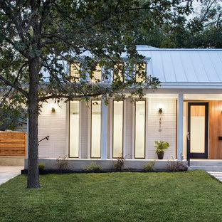 Immagine della facciata di una casa unifamiliare piccola bianca contemporanea a un piano con rivestimenti misti, tetto a capanna e copertura in metallo o lamiera