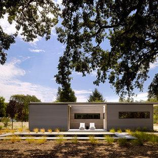 Ispirazione per la facciata di una casa piccola grigia moderna a un piano con rivestimento in metallo e tetto piano