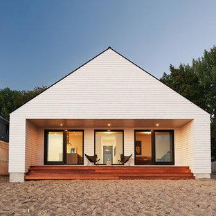 На фото: маленький, одноэтажный, деревянный, белый частный загородный дом в скандинавском стиле с двускатной крышей и металлической крышей