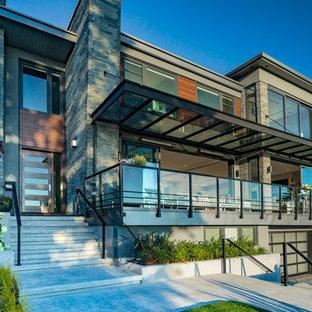 Modern inredning av ett stort grått hus, med tre eller fler plan, blandad fasad och platt tak