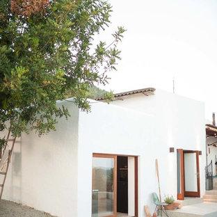 Foto de fachada blanca, mediterránea, de tamaño medio, de dos plantas, con revestimientos combinados y tejado plano
