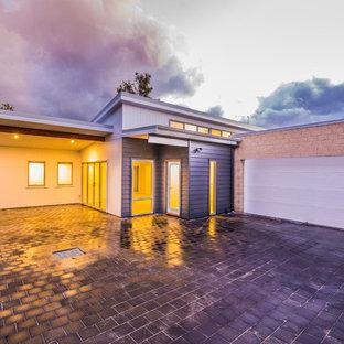 Foto de fachada de casa multicolor, moderna, pequeña, de una planta, con revestimiento de aglomerado de cemento, tejado plano y tejado de metal