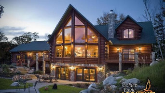 Incredible exterior view of a log home with prow widow wall