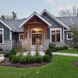 Diseño de fachada de casa azul, de estilo americano, grande, de una planta, con revestimiento de hormigón, tejado a dos aguas y tejado de teja de madera