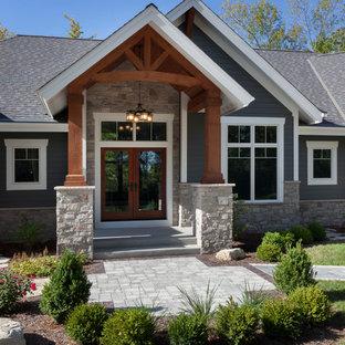 Modelo de fachada de casa gris, de estilo americano, grande, de una planta, con revestimiento de hormigón, tejado a dos aguas y tejado de teja de madera