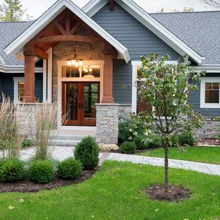Exempel på ett stort amerikanskt blått hus, med allt i ett plan, sadeltak och tak i shingel