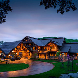 Example of a mountain style brown two-story wood exterior home design in Other with a tile roof