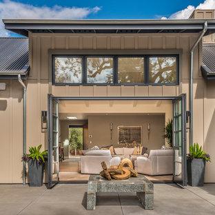 Modelo de fachada de casa marrón, campestre, grande, de dos plantas, con revestimiento de madera, tejado a dos aguas y tejado de metal