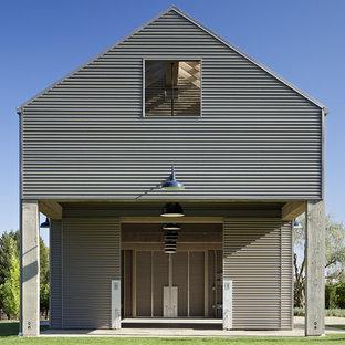 Imagen de fachada gris, urbana, de dos plantas, con revestimiento de metal y tejado a dos aguas