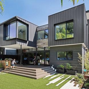 Imagen de fachada negra, moderna, de tres plantas, con revestimiento de metal y tejado plano