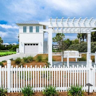 Ejemplo de fachada blanca, marinera, pequeña, de dos plantas, con revestimiento de madera, tejado a cuatro aguas y tejado de metal