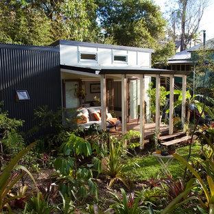 Diseño de fachada verde, actual, pequeña, a niveles, con revestimiento de aglomerado de cemento y tejado de un solo tendido