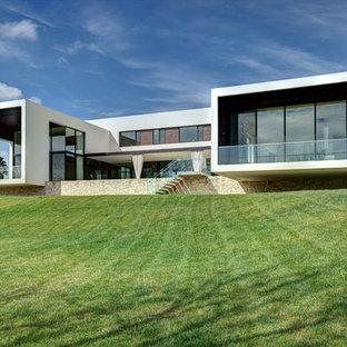 Exempel på ett stort modernt vitt hus, med två våningar, glasfasad och platt tak