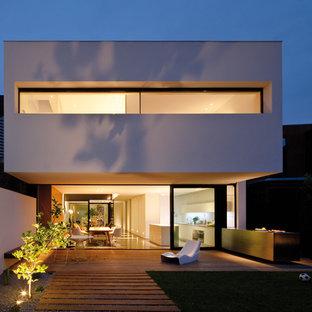 Foto della facciata di una casa grande bianca moderna a due piani con rivestimento in cemento e tetto piano