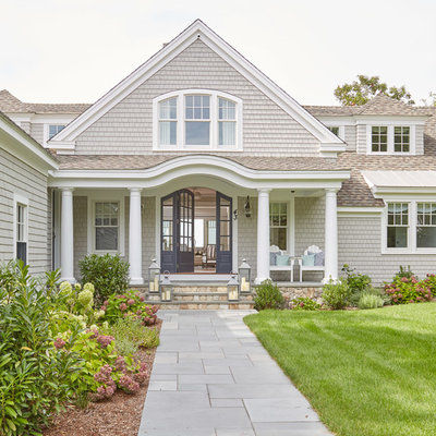 Example of a mid-sized classic gray two-story exterior home design in Boston with a shingle roof