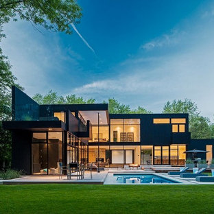 Large minimalist black two-story flat roof photo in Other