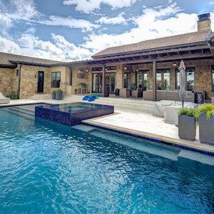Ispirazione per la facciata di una casa unifamiliare ampia multicolore mediterranea a due piani con rivestimento in pietra, tetto a capanna e copertura a scandole