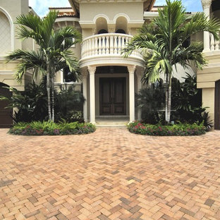 Example of a tuscan gray two-story exterior home design in Miami