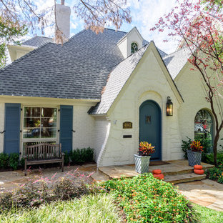 Inspiration for a timeless beige two-story brick gable roof remodel in Dallas