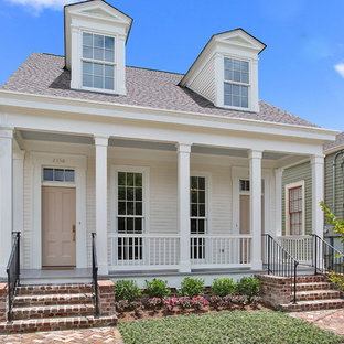 Example of a mid-sized classic white one-story wood exterior home design in New Orleans with a shingle roof