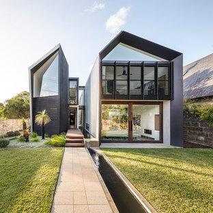 Imagen de fachada de casa negra, contemporánea, de dos plantas, con revestimiento de metal, tejado de metal y tejado a dos aguas