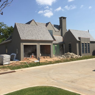 Large minimalist gray two-story stucco exterior home photo in Austin with a tile roof