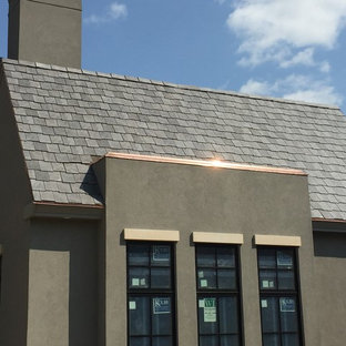 Example of a large minimalist gray two-story stucco exterior home design in Austin with a tile roof