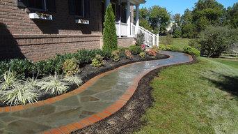Irregular flagstone walkway with a brick border.