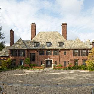 Idee per la facciata di una casa unifamiliare rossa classica a due piani con rivestimento in mattoni, tetto a padiglione e copertura a scandole