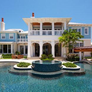 マイアミのトロピカルスタイルのおしゃれな家の外観 (青い外壁) の写真