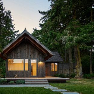 Foto de fachada de casa negra, minimalista, de una planta, con revestimiento de madera, tejado a dos aguas y tejado de metal