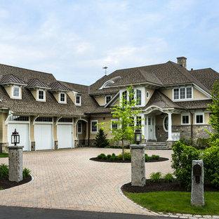 Imagen de fachada beige, marinera, extra grande, de dos plantas, con revestimientos combinados, tejado a cuatro aguas y tejado de teja de madera