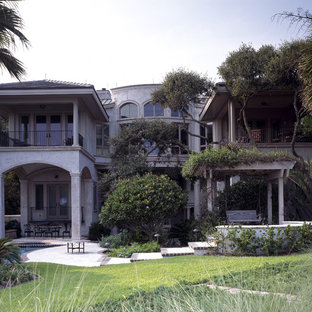 Inspiration for a large mediterranean beige two-story stucco exterior home remodel in Atlanta with a hip roof