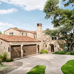 Mediterranean multicolored two-story stone exterior home idea in Austin with a tile roof