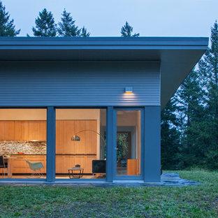 Réalisation d'une façade de maison marron design de taille moyenne et de plain-pied avec un toit plat et un toit végétal.