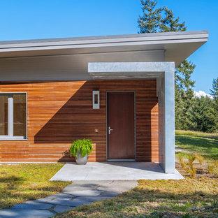 На фото: одноэтажный, деревянный, коричневый частный загородный дом среднего размера в современном стиле с плоской крышей и зеленой крышей