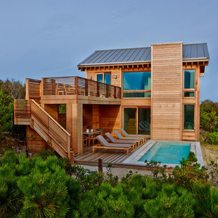 Huge beach style brown two-story wood exterior home idea in New York with a metal roof