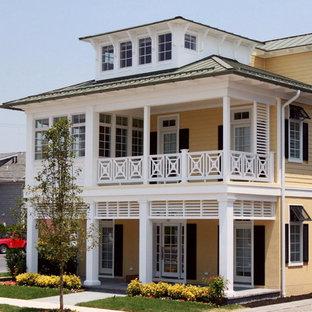 Ejemplo de fachada de casa amarilla, costera, grande, de tres plantas, con revestimientos combinados, tejado a cuatro aguas y tejado de metal