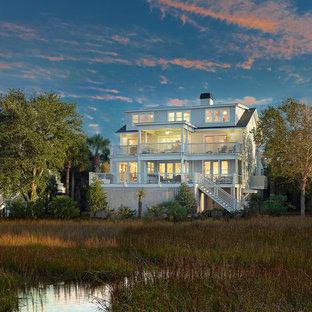 Modelo de fachada gris, costera, grande, de tres plantas, con revestimiento de madera y tejado de un solo tendido