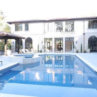 Inspiration för ett mycket stort medelhavsstil vitt hus, med två våningar, stuckatur, valmat tak och tak med takplattor